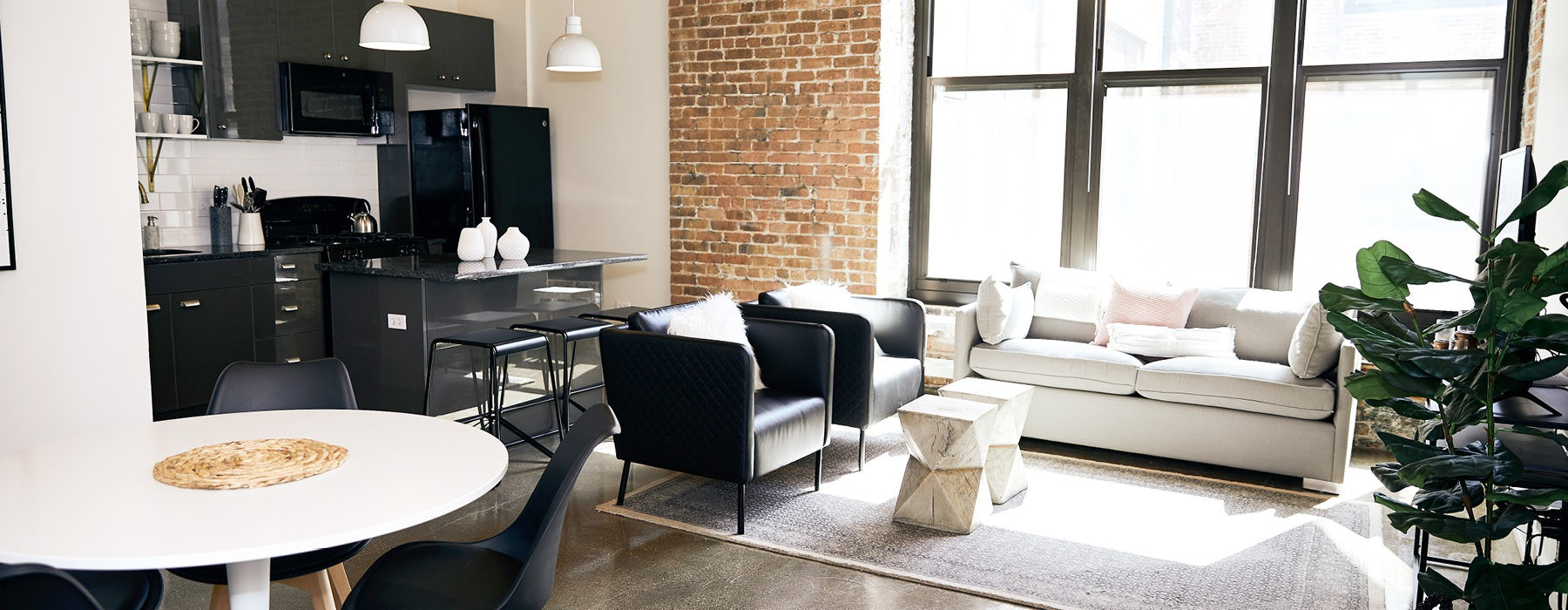 spacious, loft style apartment with concrete floors, brick walls and large windows