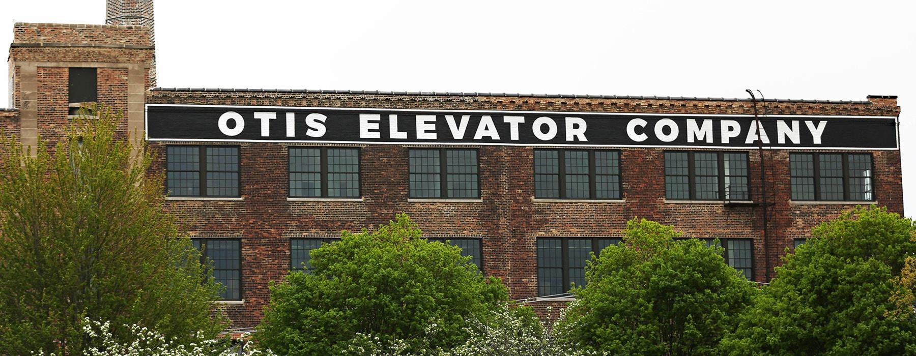 Otis Elevator Company sign across the newly renovated brick, Otis Apartment building